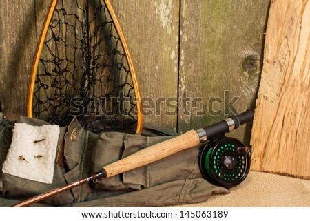 Fly fishing gear on burlap against cedar wood wall - stock photo