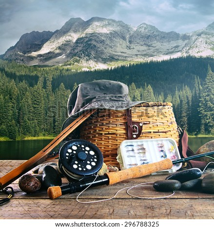 Fly fishing gear on wooden deck with lake in background - stock photo