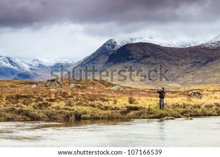 Fly fishing in a river with snow covered mountains in the back - stock photo