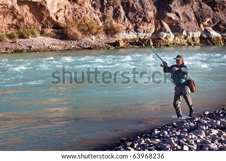 Fly-fishing on mountain river - stock photo