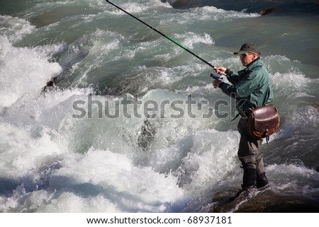 Fly fishing on mountain river - stock photo