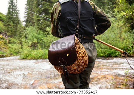 Fly fishing on the creek in mountain forest - stock photo