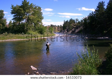 Fly-fishing on the Crowsnest River, Alberta, Canada; late summertime; blue skies; river and trees - stock photo