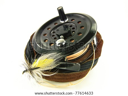 Fly Fishing Reel:  A well-used fishing reel sits atop its leather case along with a lure made for fly-fishing. - stock photo