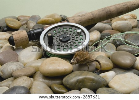 Fly fishing rod and reel with artificial mouse lure. - stock photo