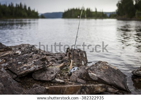 Fly fishing rod at the water front at a lake.