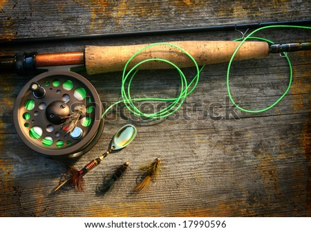 Fly fishing rod with  on wood background - stock photo