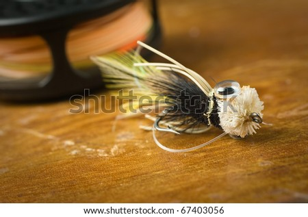 Fly fishing tackle, large fly and reel. - stock photo