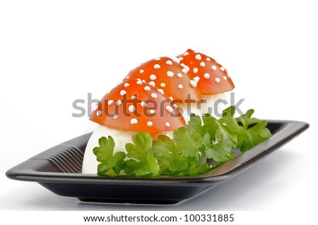 Fly mushroom formed from boiled egg, cover with the tomato mayonnaise. Funny food for children or party. - stock photo