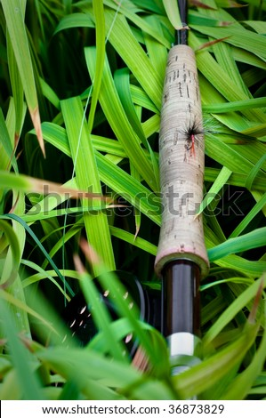 Fly rod on grass with fly on handle