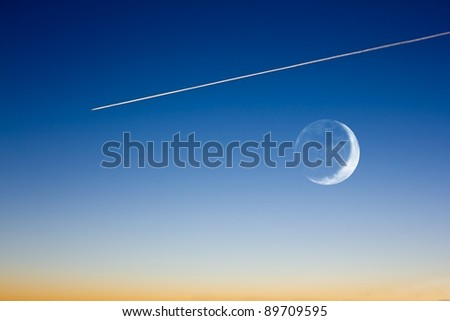 fly track and half moon on a evening sky background - stock photo