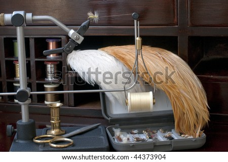 Fly tying equipment and materials in preparation of making trout flies - stock photo