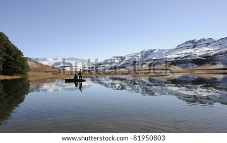 flyfishing for trout against a backdrop of snow at giants cup wilderness reserve, kwazulu natal, south africa - stock photo