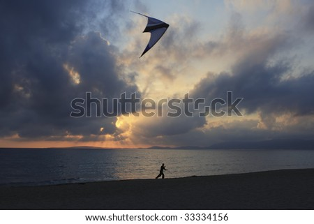 Flying a kite at sunset - stock photo