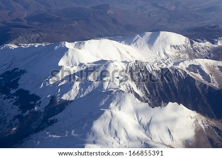 Flying above mountains: snow below - stock photo