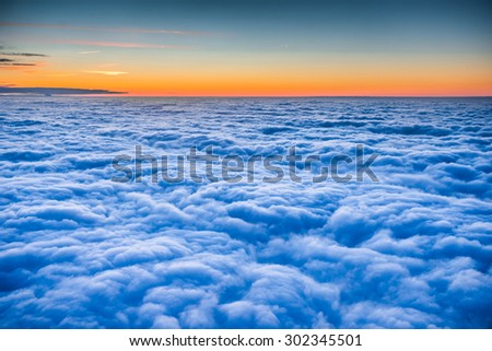 flying above the beautiful clouds in the evening sky - stock photo