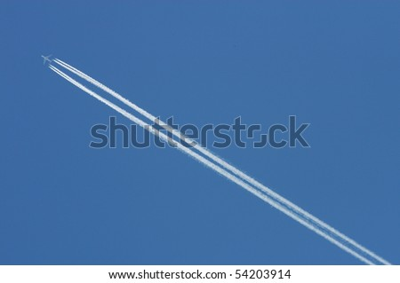 Flying airoplane on the blue sky leaving white lines behind - stock photo