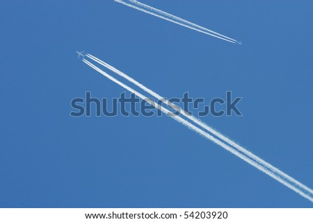 Flying airoplanes on the blue sky leaving white lines behind - stock photo