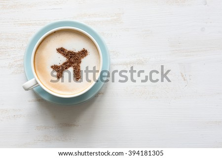 Flying airplane made of cinnamon in cappuccino. White background. Traveling concept. Airport cafe. Copy space for text - stock photo