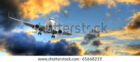 Flying away: panorama of airplane taking off in dramatic sunset sky with copy space. - stock photo