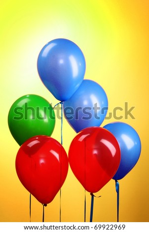 Flying balloons on yellow background