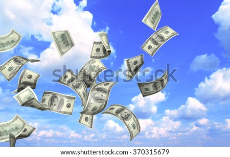 Flying banknotes of dollars on blue sky background - stock photo