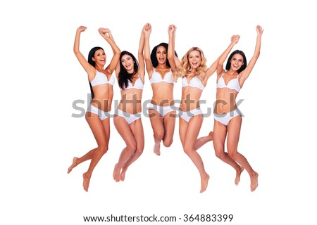 Flying beauties. Full length of five beautiful women in lingerie jumping and keeping arms raised against white background