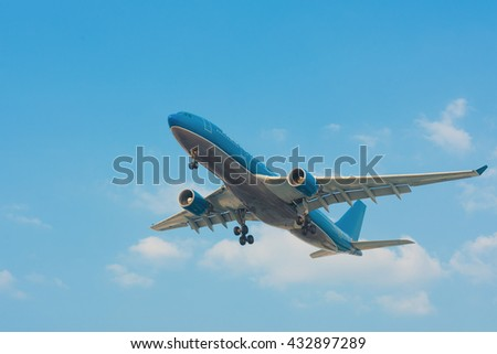 flying blue and grey airplane in blue sky - stock photo