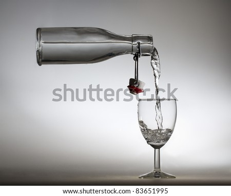 Flying bottle pouring water in glass - stock photo
