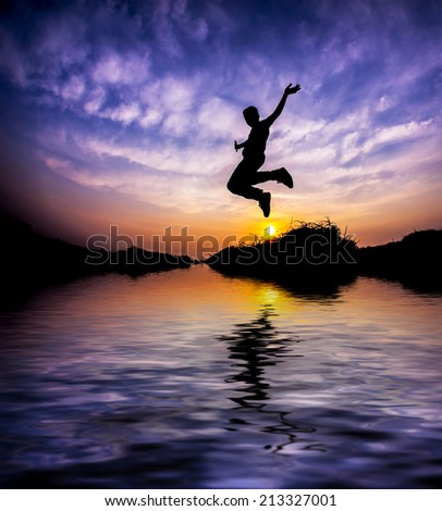 Flying boy during sunset in Silhouette. digital compositing, colour tone, water reflection and ripple effects. - stock photo