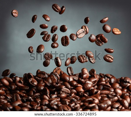 Flying coffee beans over dark background - stock photo