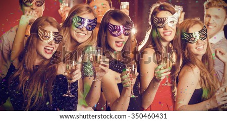 Flying colours against friends in masquerade masks drinking champagne - stock photo
