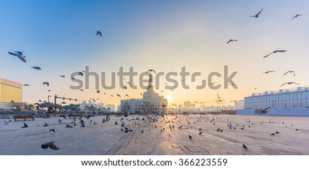 Flying doves over FANAR, Qatar Islamic Cultural Center in Doha - stock photo
