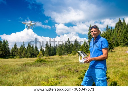 Flying drone in mountain scenario with pilot controlling it. - stock photo
