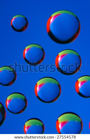 Flying drops on the blue background... (1) - stock photo