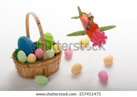 Flying Easter bunny with Easter basket and eggs - stock photo