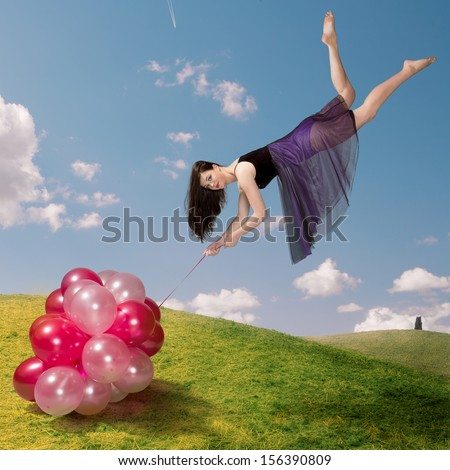 Flying girl holding colorful balloons - stock photo