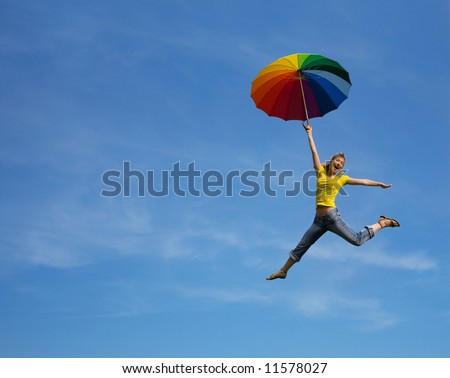 Flying girl with colorful umbrella on the blue blue sky - stock photo