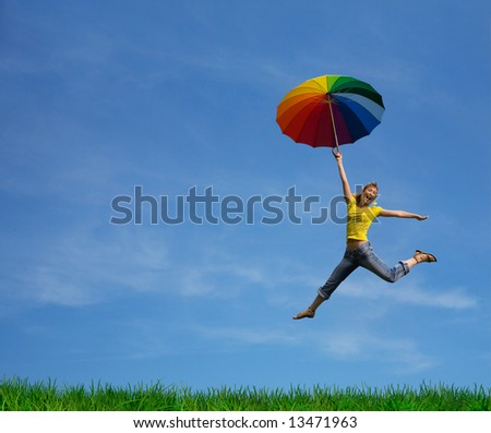 Flying girl with colorful umbrella on the green green grass - stock photo