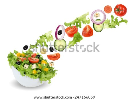Flying green salad in bowl with tomatoes, Feta cheese, onion, olives and cucumber