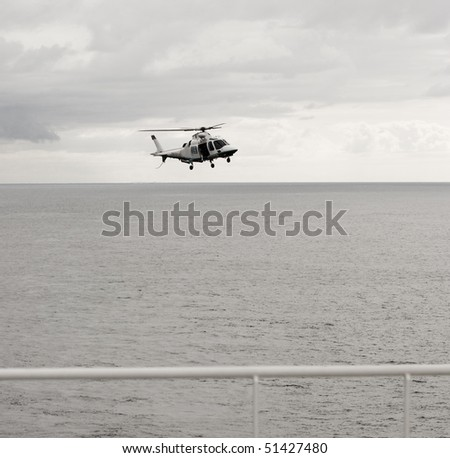 Flying helicopter on sky and sea background - stock photo