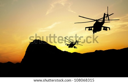 Flying helicopter silhouettes on sunset background - stock photo
