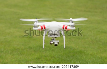 Flying helicopter with camera over grass - stock photo