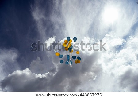 Flying in the sky yellow - blue balls.  - stock photo