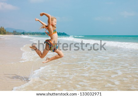 flying jump beach girl on blue sea shore in summer vacation - stock photo