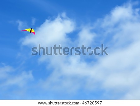 flying kite over blue sky and clouds background - stock photo