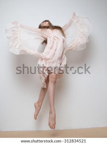 Flying little girl in a beautiful dress in a studio - stock photo