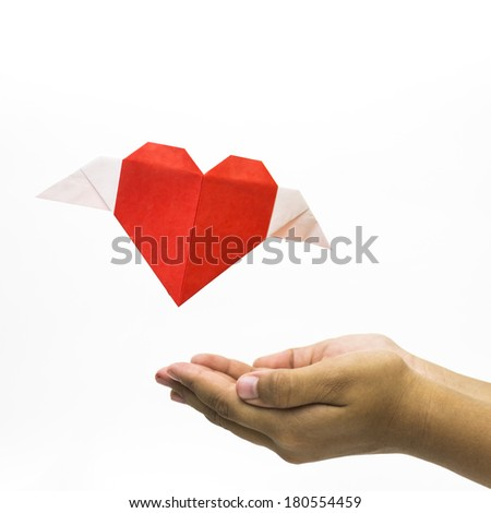 Flying love shape origami with hand at bottom - stock photo
