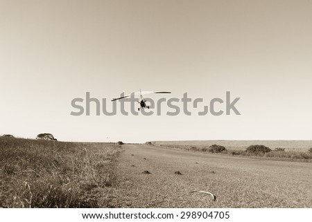 Flying Microlight Plane Sepia Flying microlight aircraft plane take off flight on rural countryside grass airstrip in vintage sepia tone - stock photo