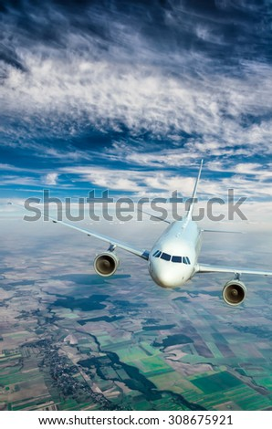 Flying of a passenger plane over the land - stock photo